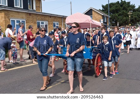 WHITSTABLE, UK-JULY 26: Members of the Whitstable Sea scouts pull the stall of oysters in the Oyster Festival Parade, after the blessing of the oysters ceremony. July 26, 2014  Whitstable UK. - stock photo
