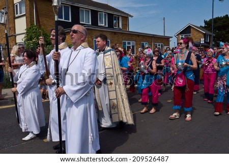 WHITSTABLE,UK-JULY 26: The Rev Simon Tillotson and clergy from St Peters  take part in the Whitstable Oyster Festival Parade, after the Blessing of the Oysters. July 26, 2014 Whitstable UK. - stock photo