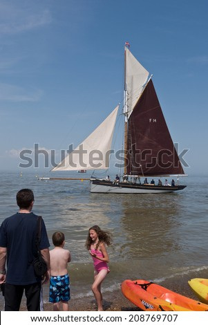 WHITSTABLE, UK-JULY 27: Visitors and boat owners enjoy the sea at Whitstable where thousands of visitors attend the annual Whitstable Oyster Festival. July 27, 2014 , Whitstable Kent UK. - stock photo