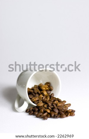 Who spilled the beans? A cup of coffee beans tipped over on a white background - stock photo