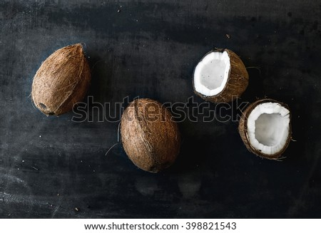 Whole and broken coconuts over dark grunge backdrop, horizontal - stock photo