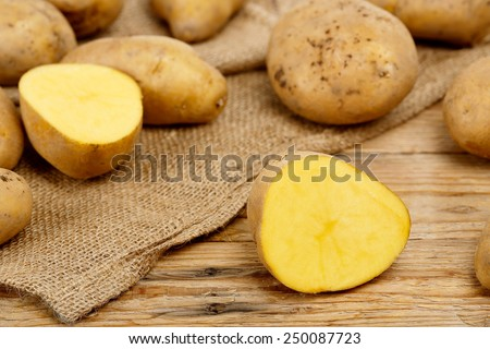 whole and cut potatoes on burlap sack and wood - stock photo