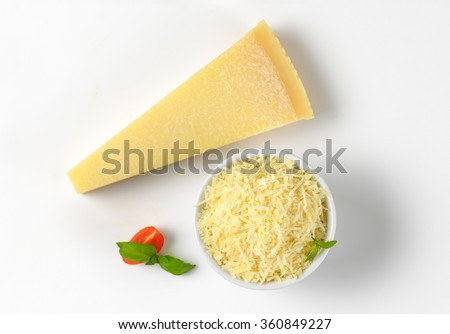 whole and grated parmesan cheese on white background - stock photo
