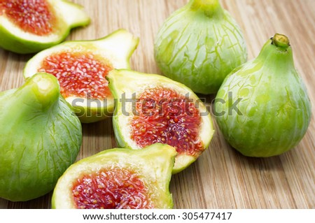 Whole and Sliced Green Figs on a Wooden Cutting Board - stock photo