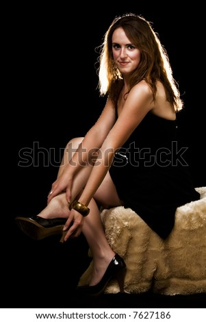 Whole body of an attractive young brunette woman in black dress  sitting on a fur covered stool over black - stock photo
