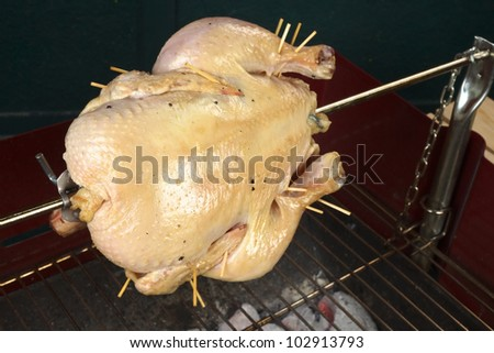 Whole chicken being grilled on spit over a charcoal barbecue (Selective Focus, Focus on the front of the chicken) - stock photo