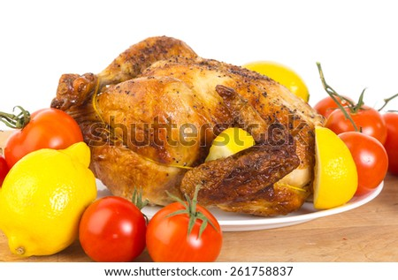 Whole Chicken seasoned with pepper and lemon juice and roasted on rotisserie on white plate with lemons and tomatoes on wooden cutting board against white background with copy space. - stock photo