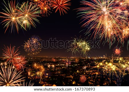 Whole city celebrating the New Year or any national event with fantastic multi-colored fireworks, copyspace on the night sky - stock photo