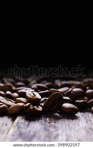 Whole coffee beans on a wooden background. Selective focus. - stock photo