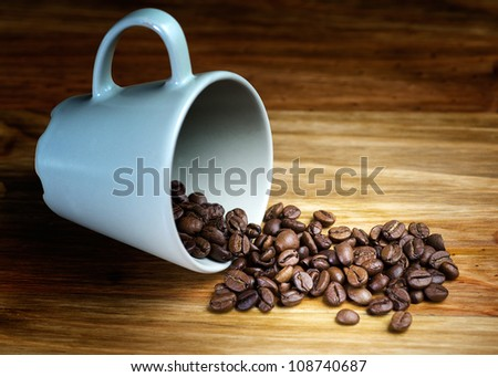whole coffee beans spilled on wooden table with cup - stock photo