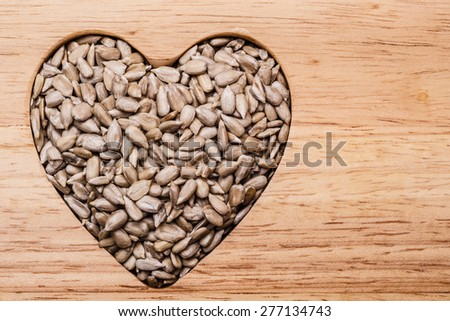 Whole food. Heart shaped sunflower seeds on wood surface background - stock photo