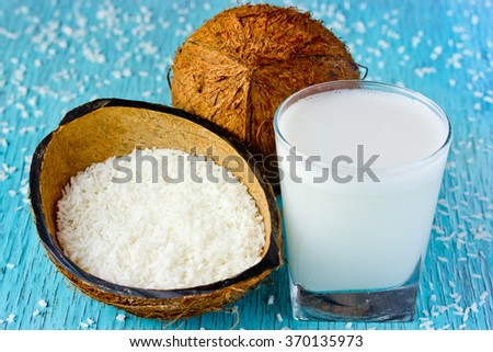 Whole fresh coconut, coconut chips and coconut milk in a glass on a blue background. Hair treatment and cooking ingredient, selective focus - stock photo