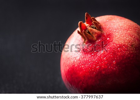 Whole fresh juicy pomegranate with water droplets on a dark background with copy space, closeup, selective focus