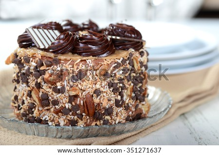 Whole German Chocolate Cake with plates and Champagne glasses - stock photo