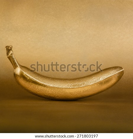 Whole golden banana on gold background - stock photo