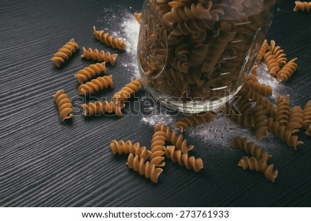 Whole grain pasta in a mason jar with flour - stock photo