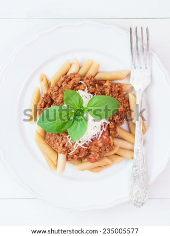 Whole grain penne pasta with vegetarian Bolognese sauce and Parmesan cheese, basil leaves on the top, silver fork on the side. White plate and wooden table in the background. Vertical, overhead view - stock photo