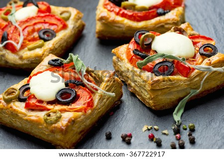 Whole grain puff pastry with tomatoes, mozzarella cheese, olives and marjoram - stock photo