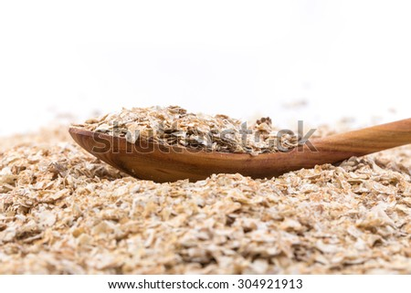 Whole grain, rolled oats flakes with wooden spoon - stock photo