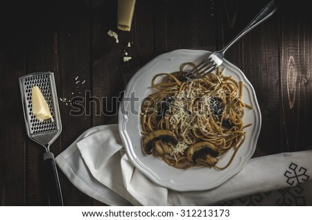 Whole grain spaghetti with mushrooms and parmesan cheese, dark picture, focus on detail and darkness - stock photo
