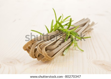 Whole grain tagliatelle with fresh rosemary on wooden table. - stock photo