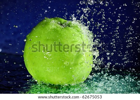 Whole green apple with stopped motion water drops on deep blue - stock photo