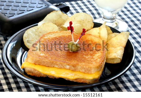 Whole grilled cheese sandwich with chips and sandwich maker. - stock photo