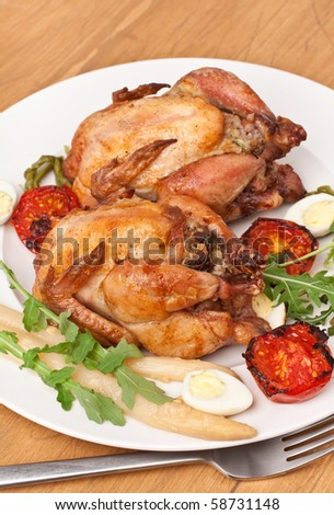 whole grilled chickens garnished with vegetables - stock photo