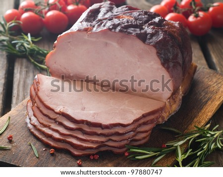 Whole ham with tomato in the background, selective focus - stock photo