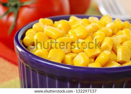 Whole kernel sweet corn in purple ramekin with fresh tomatoes and fork in background.  Macro with shallow dof. - stock photo