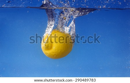 Whole lemon dropped in water against gradient blue background - stock photo