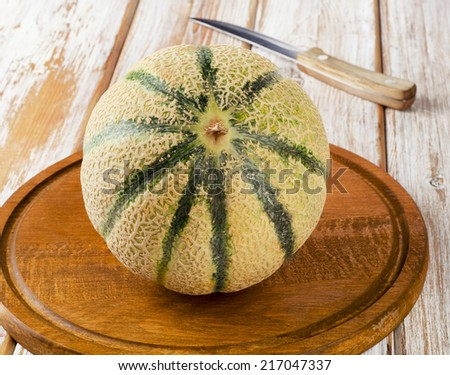 Whole melon  on a wooden table. Selective focus - stock photo