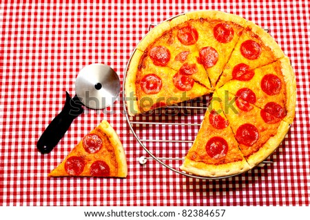Whole pepperoni pizza with slice removed and cutter.  Pizza is on rack with cutter on table.  Items are on red gingham tablecloth. - stock photo