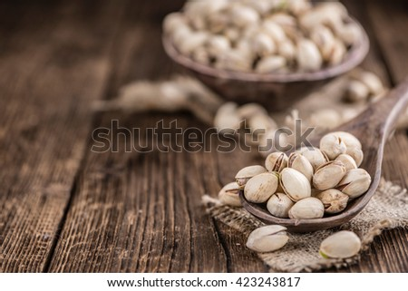 Whole Pistachios (detailed close-up shot; selective focus) on wooden background - stock photo