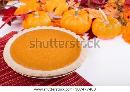 Whole pumpkin pie with autumn colors and decor - stock photo