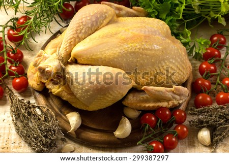 whole raw chicken on a cutting board - stock photo