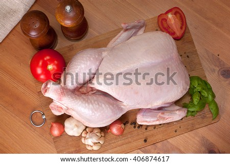Whole raw chicken on a wooden table - stock photo