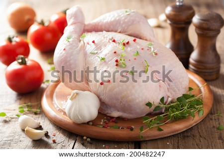 whole raw chicken with rose pepper and thyme  - stock photo