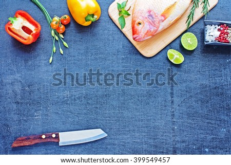 Whole raw fish (Nile tilapia) with lime, herbs and spices. Bell pepper, cherry tomato, young garlic and sharp knife on a dark wooden board. Space for text. - stock photo