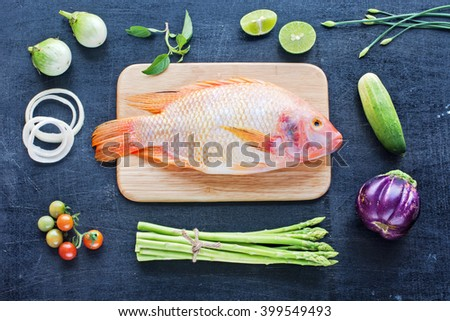 Whole raw fish with herbs. Farm vegetables (asparagus, eggplant, cherry tomato, cucumber) on a dark wooden board. Cooking background. Healthy food / diet concept.  - stock photo