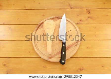 Whole raw parsnip with a sharp kitchen knife on a wooden cutting board - stock photo