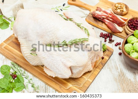 Whole raw  turkey on wooden cutting board,vegetables, ham and  spices. Viewed from above - stock photo