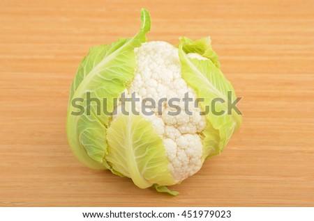 Whole ripe cauliflower, isolated on wooden background - stock photo
