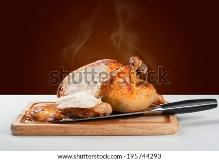 Whole roasted chicken on wooden board with a cut - stock photo