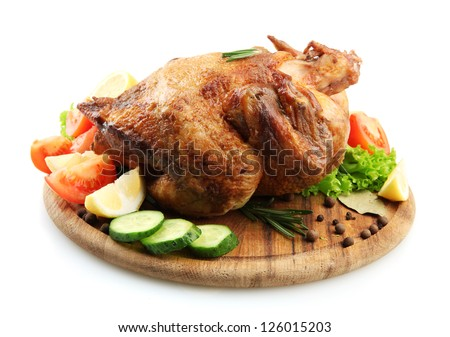 Whole roasted chicken on wooden plate with vegetables, isolated on white - stock photo