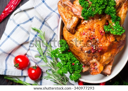 Whole Roasted Chicken with herbs and tomatoes over wooden background - stock photo