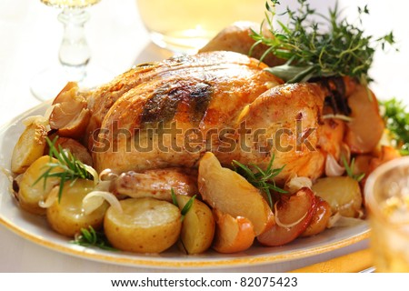 Whole roasted chicken with potatoes and apples on white plate - stock photo