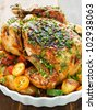 Whole roasted chicken with vegetables, herbs and fruits. Shallow dof. - stock photo