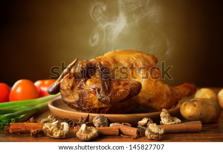 Whole roasted chicken with vegetables, on wooden tray fresh from oven with hot steam smoke, brown background - stock photo