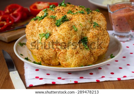 Whole roasted spicy cauliflower with mustard seeds, oil and fresh herbs - stock photo